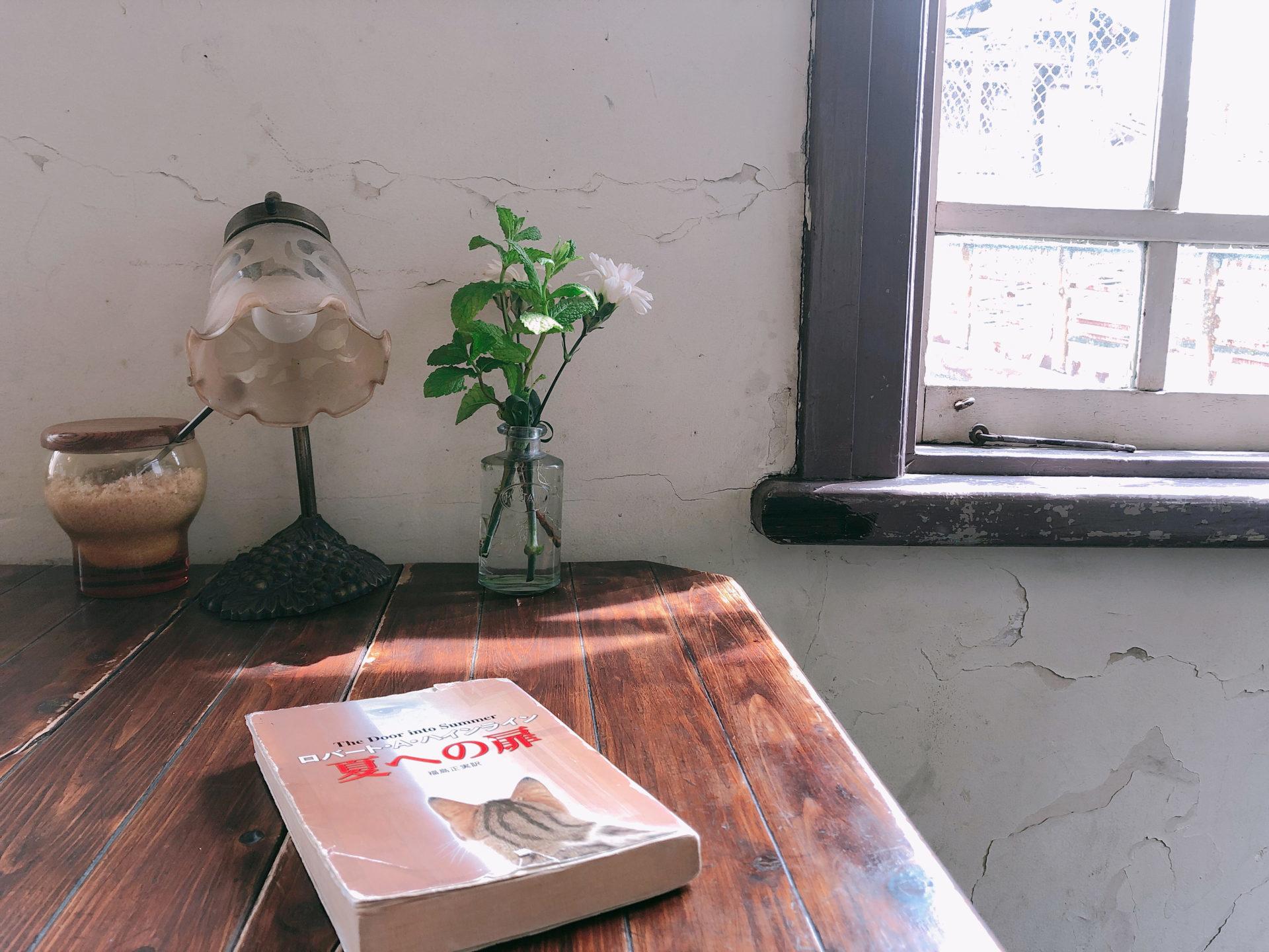 窓際のテーブルの上の本「夏への扉」