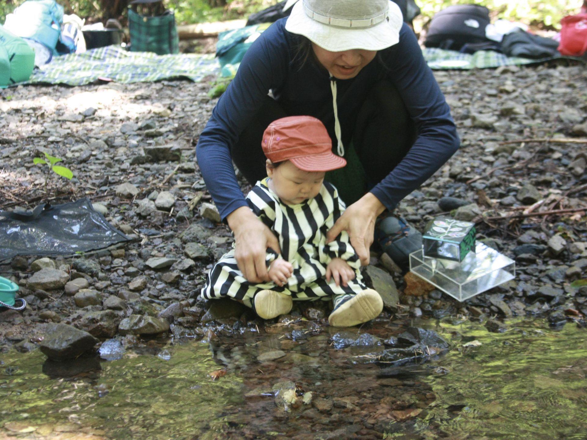 小川で遊ぶ赤ちゃん